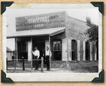 Black and white photo of two men standing outside the Cat Spring State Bank.
