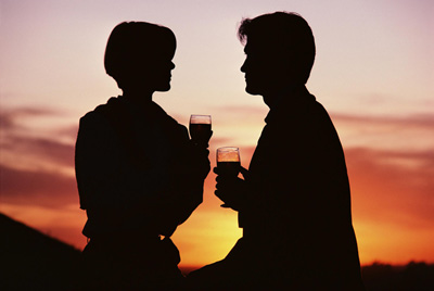 Man and woman drinking wine at sunset