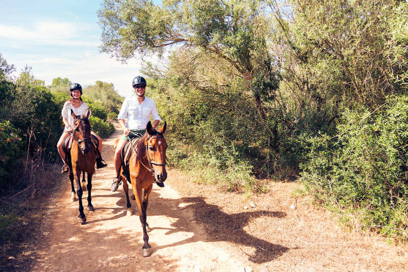 Couple horseback riding on ranch trails