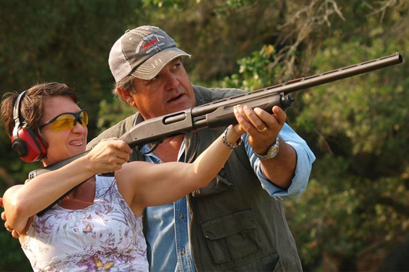 A man showing a woman how to aim a gun for trap shooting