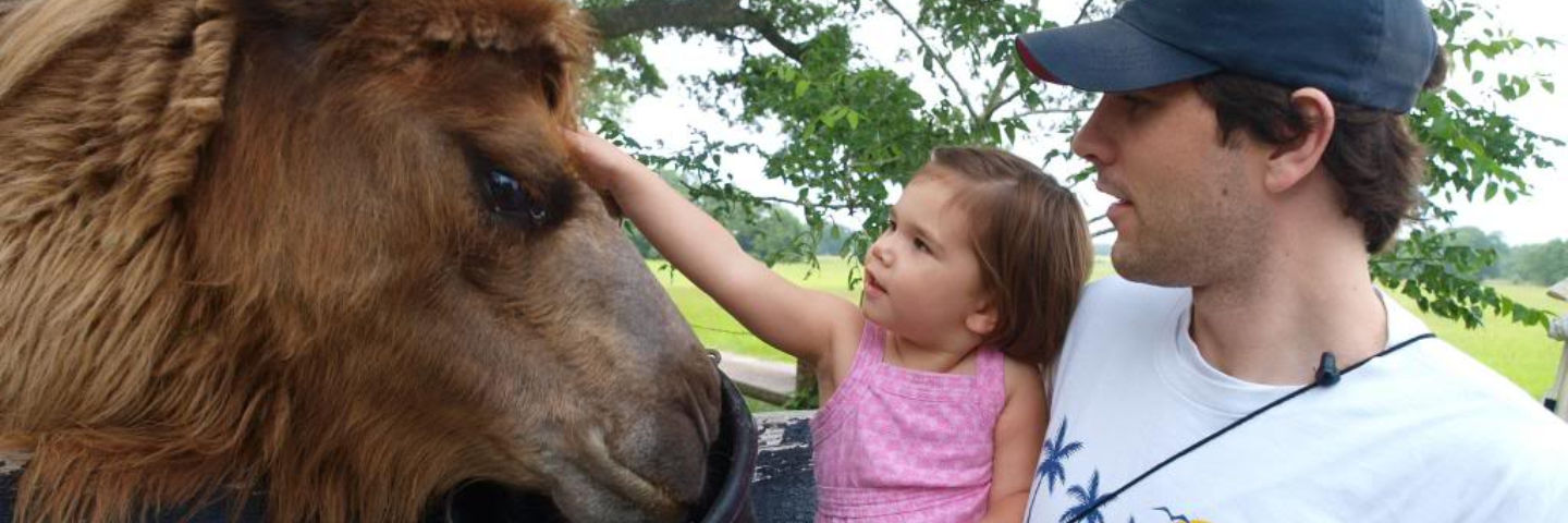 Dad holding daughter as she pet eating horse at Blisswood B&B