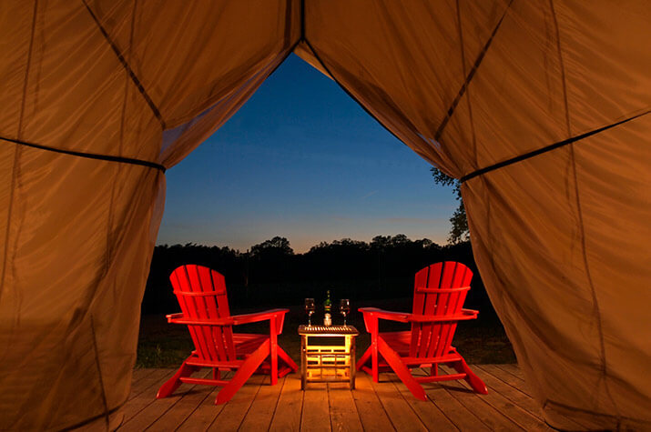 Two chairs out on a deck with glasses of wine facing sunset, Romantic Texas Getaway