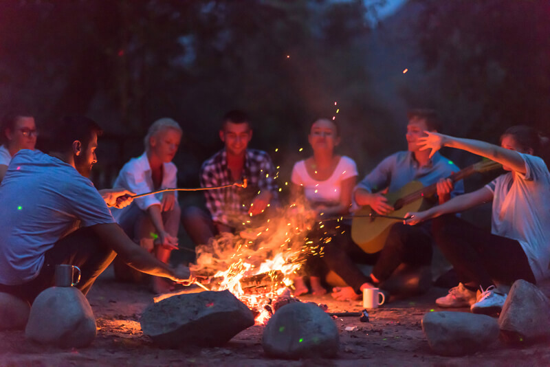 Group around camp fire at Texas adult summer camp