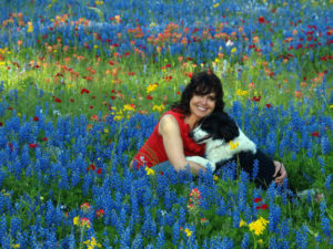 Woman with dog in a field of mostly blue flowers