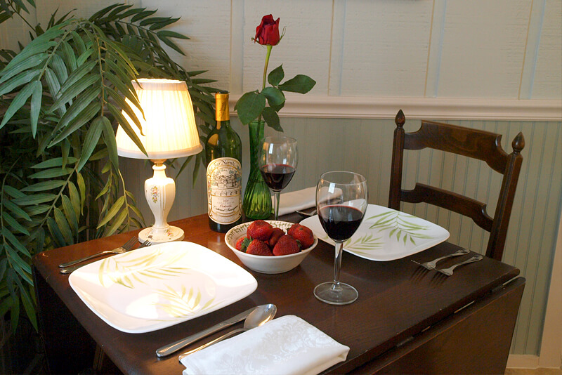 Romantic table setting with wine, rose and strawberries