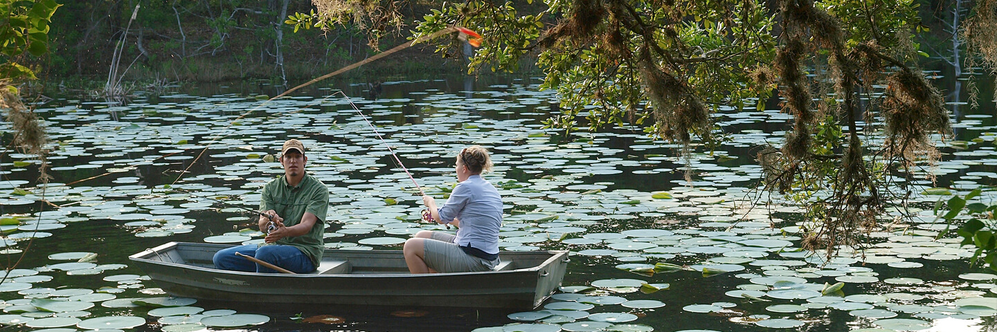 Couple fishing in a rowboat on a private lake