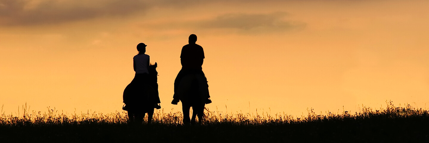 Couple on horseback riding off into the sunset on Texas ranch