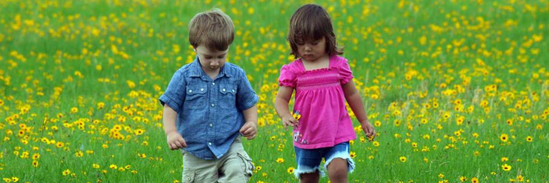 Boy and girl walking through field