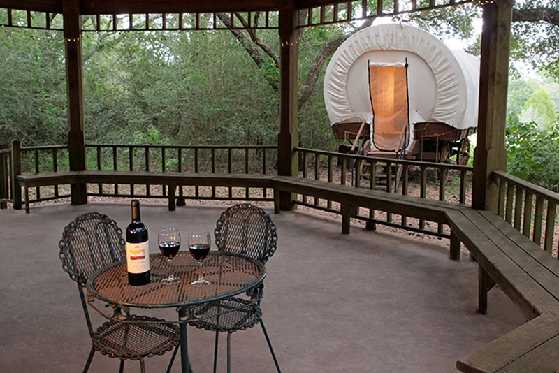 wine bottle and two glasses in the gazebo outside of the Conestoga Covered Wagon