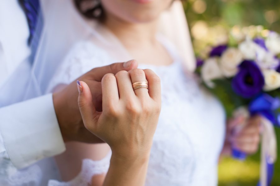 a bride and groom holding hands with ring in TX