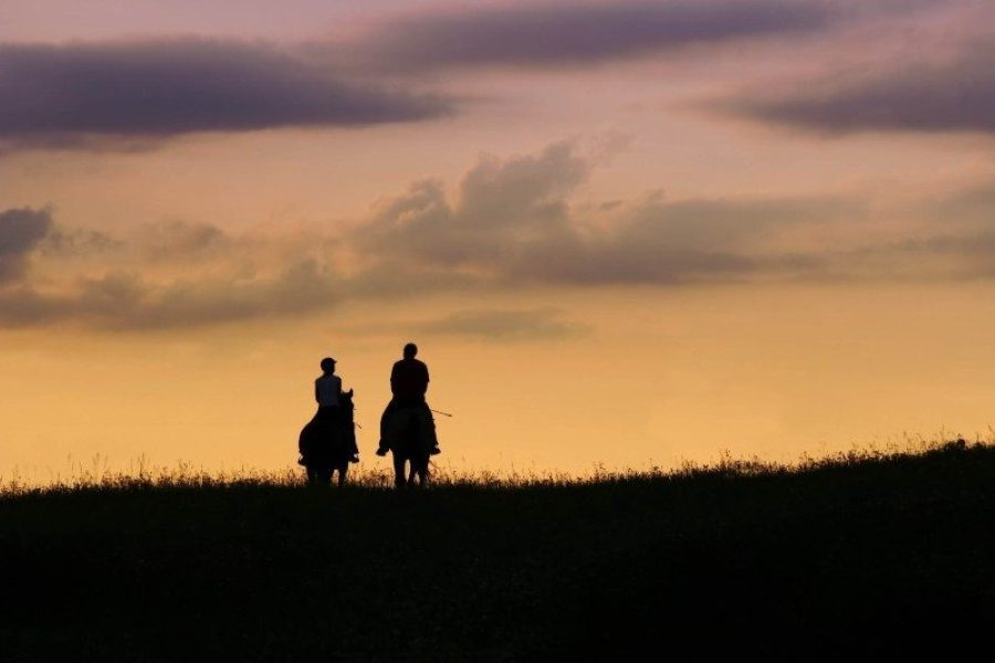 two people riding horses into the sunset