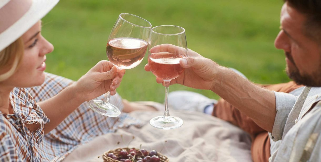 Couple on a romantic picnic toasting wine glasses