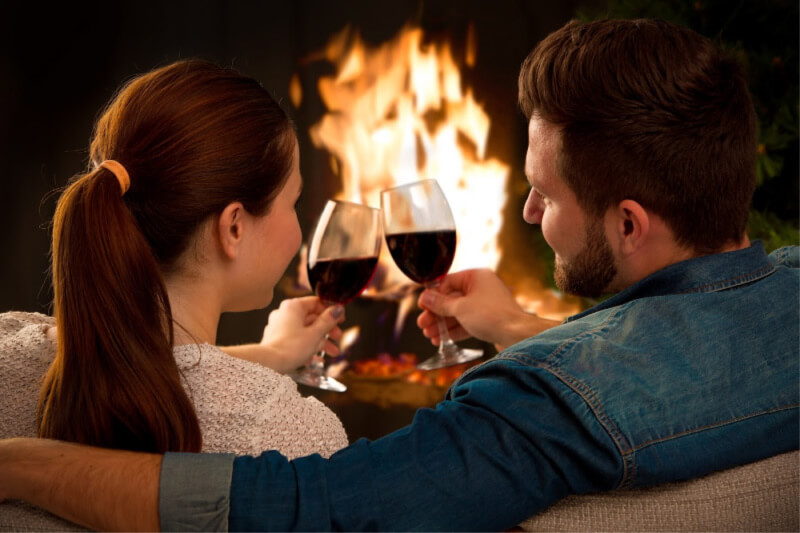 Couple drinking wine by a fireplace on romantic anniversary getaway in Texas