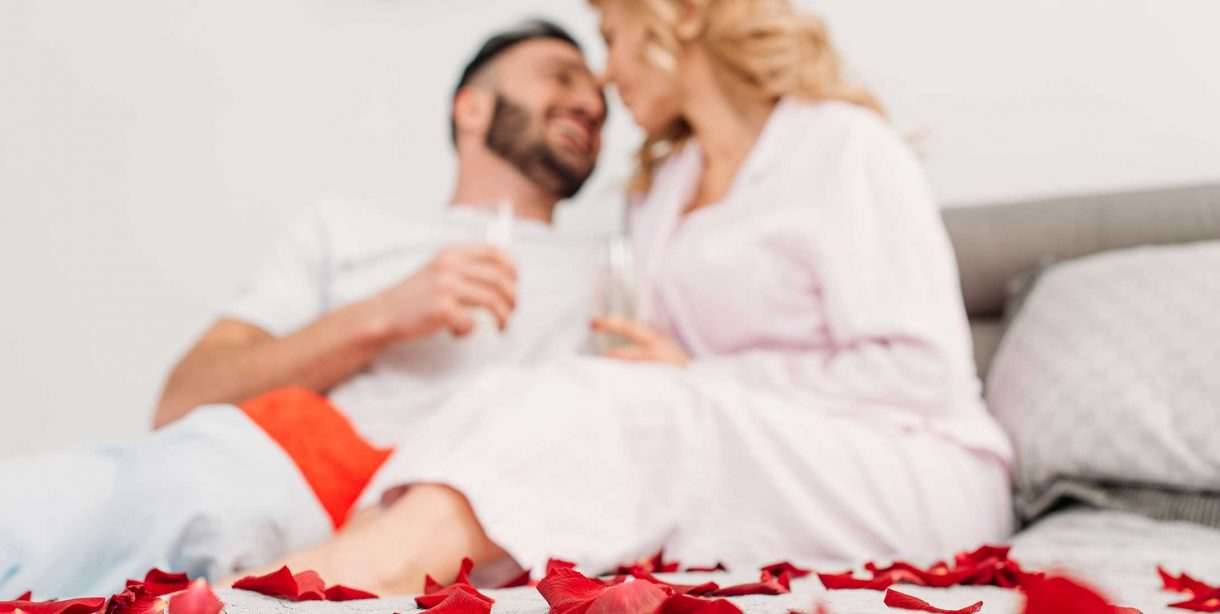 Couple having champagne on a bed with rose petals
