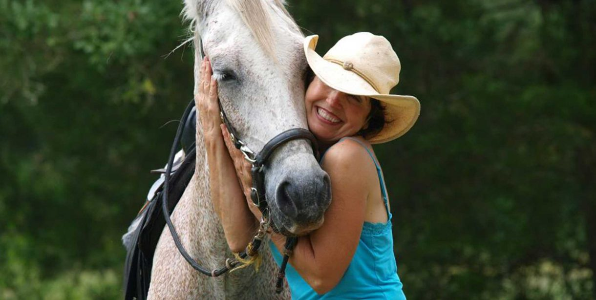 Happy woman hugging white horse