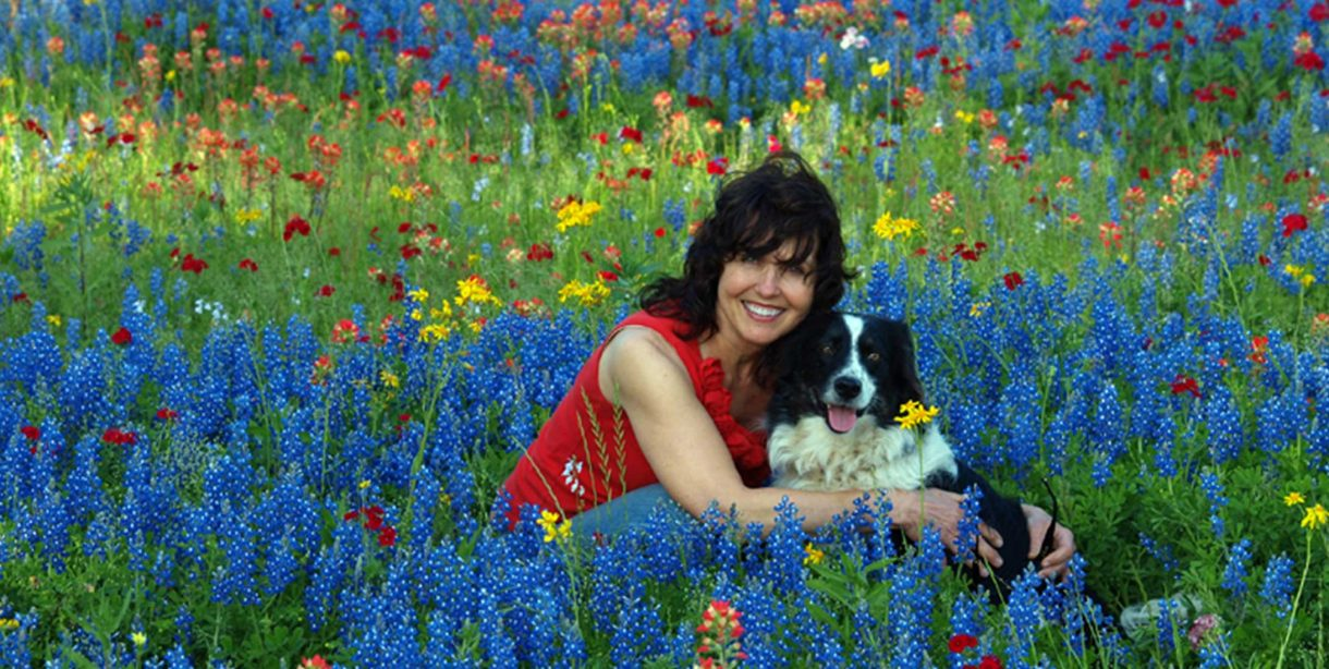 Woman hugging dog in a meadow