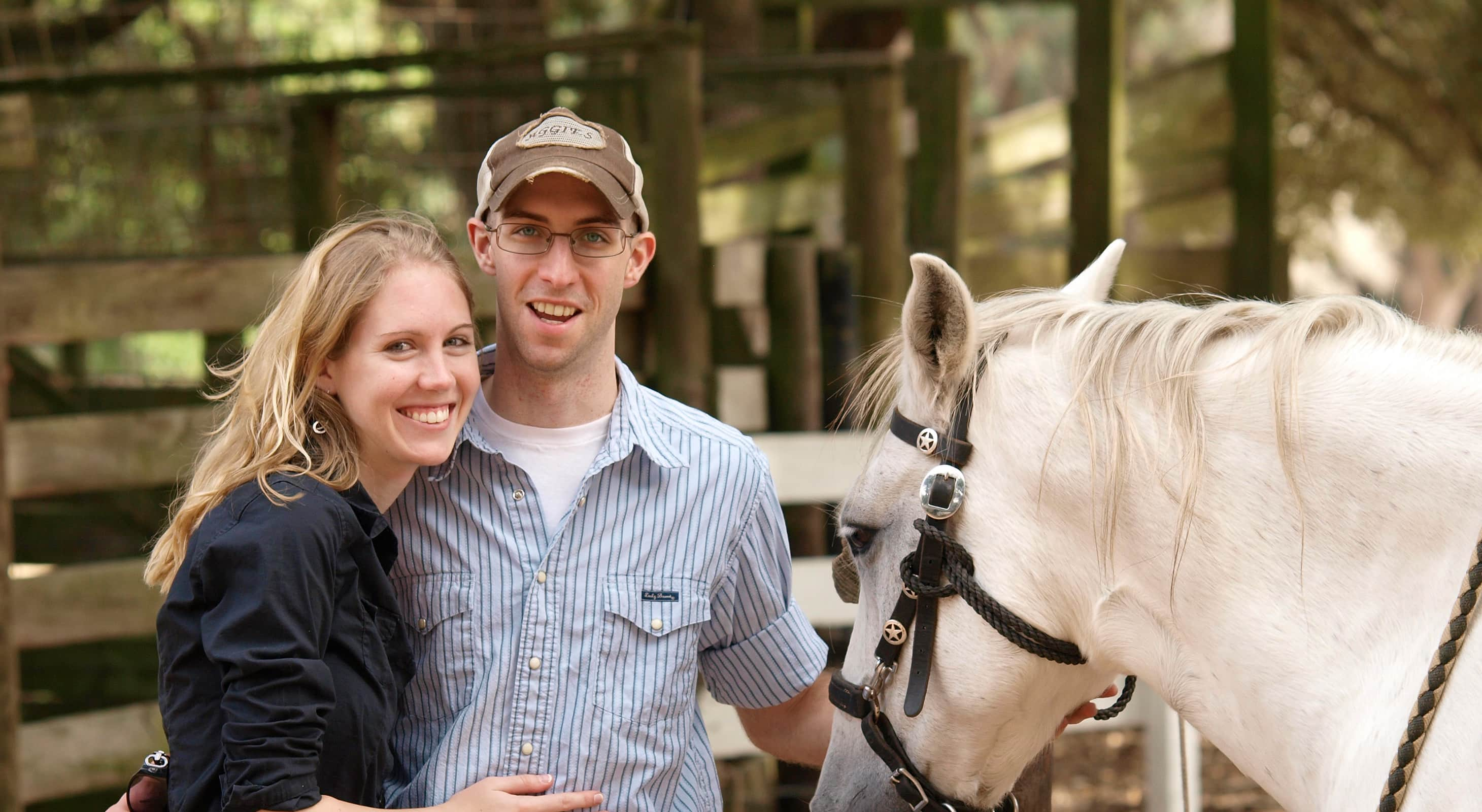 Couple standing next to a white horse
