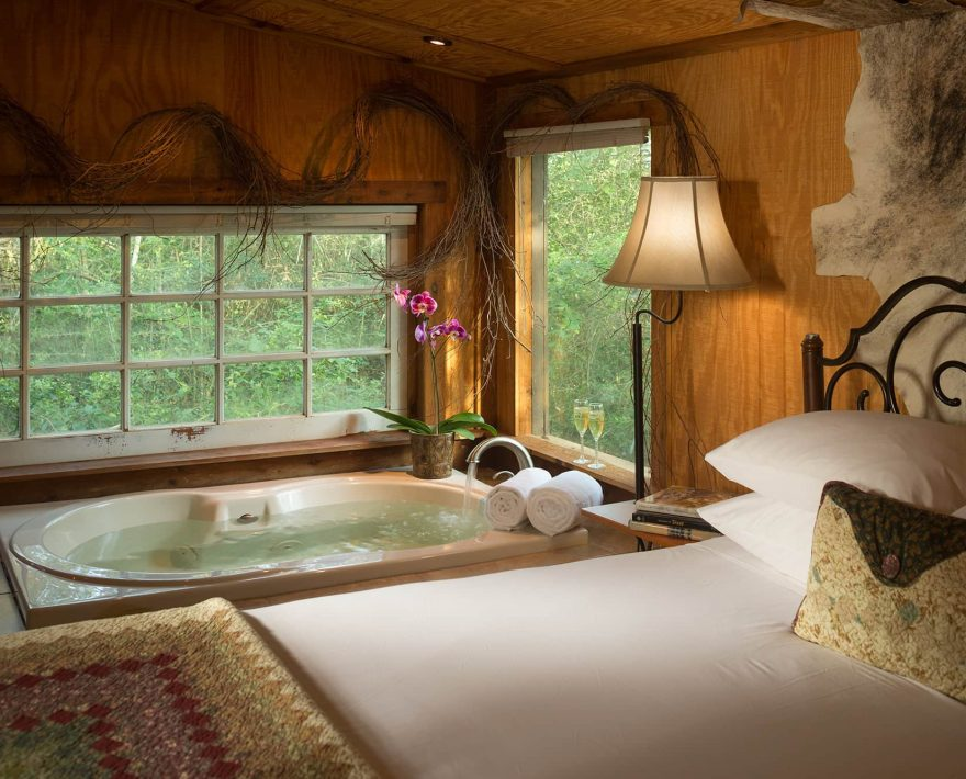 Bed and soaking tub in the Enchanted Cabin at BlissWood