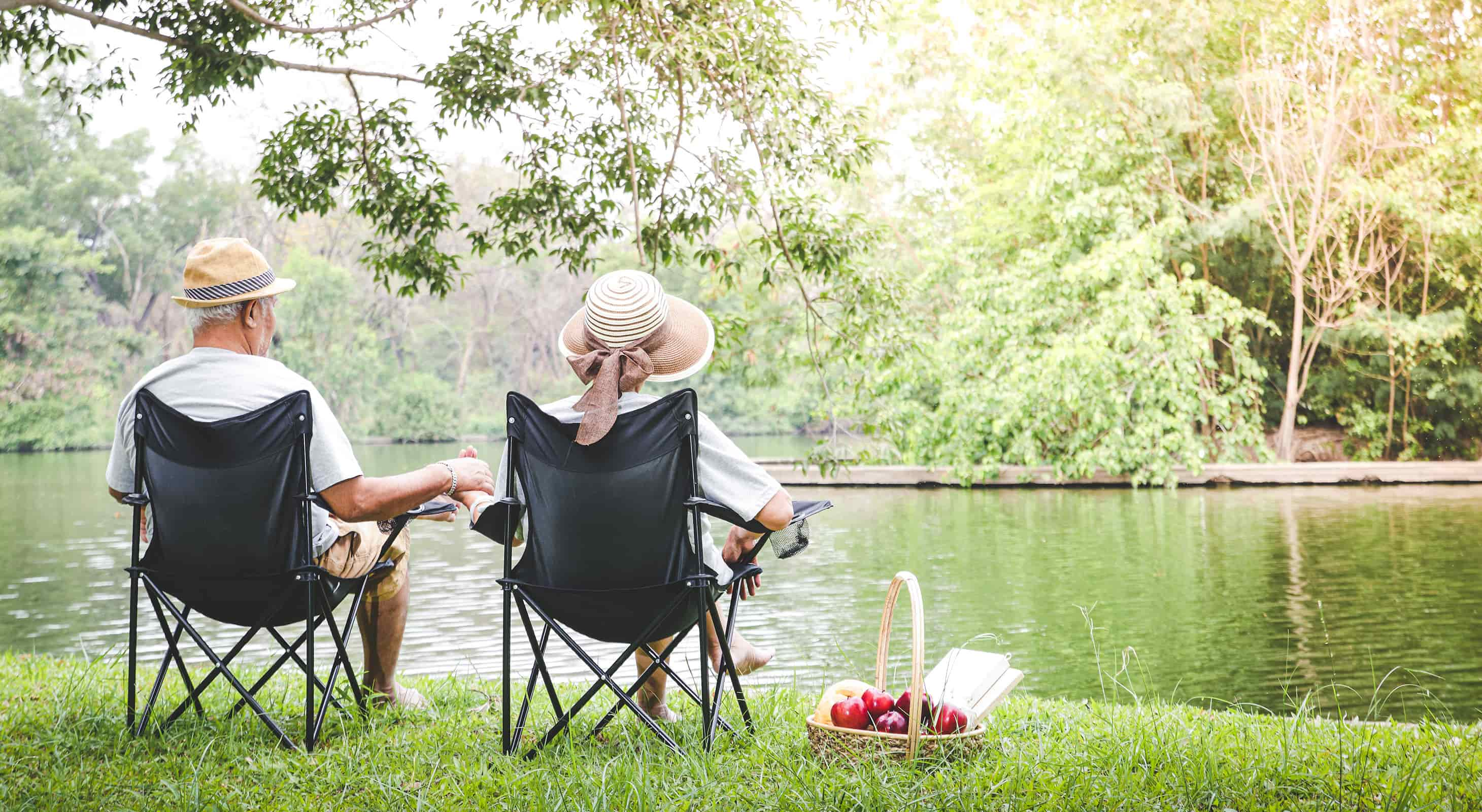 couple with chairs by the river with a picnic basket