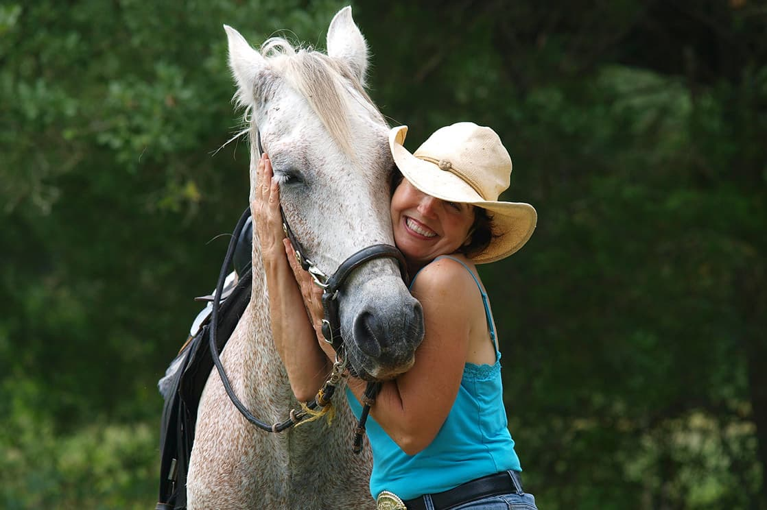 woman smiling and hugging her horse