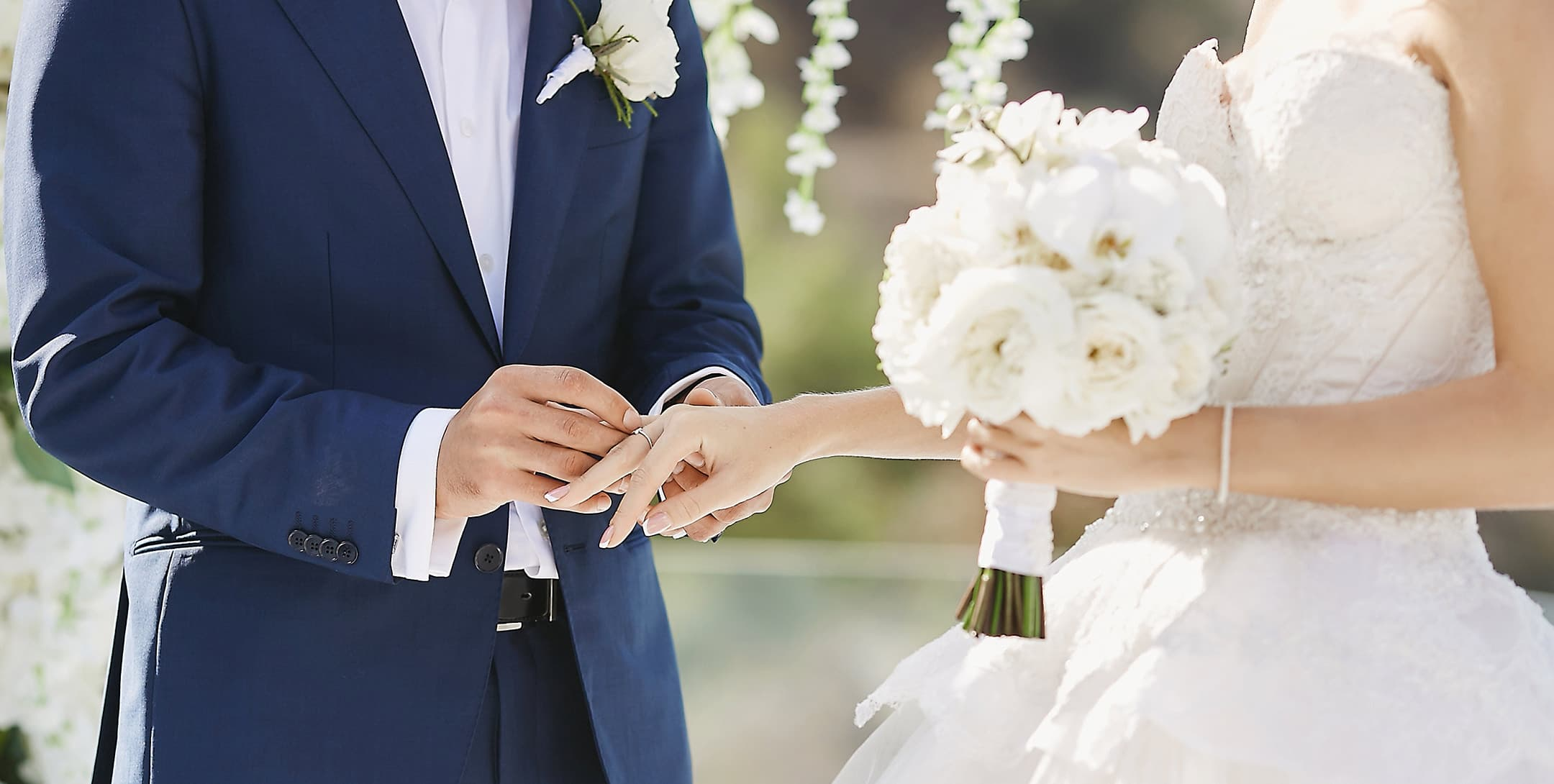 groom putting a ring on bride's finger during an outdoor ceremony