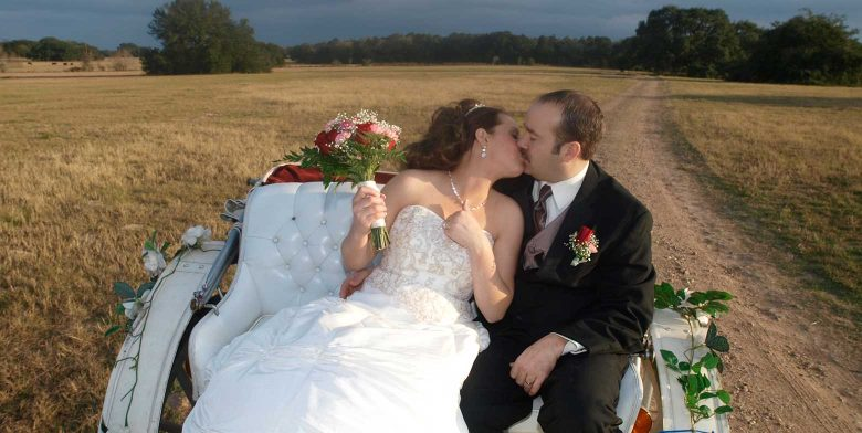 Married couple kissing on horse drawn carriage ride