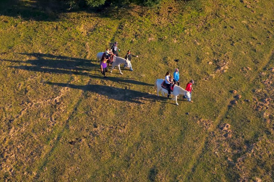 family riding horses on the ranch photographed from above