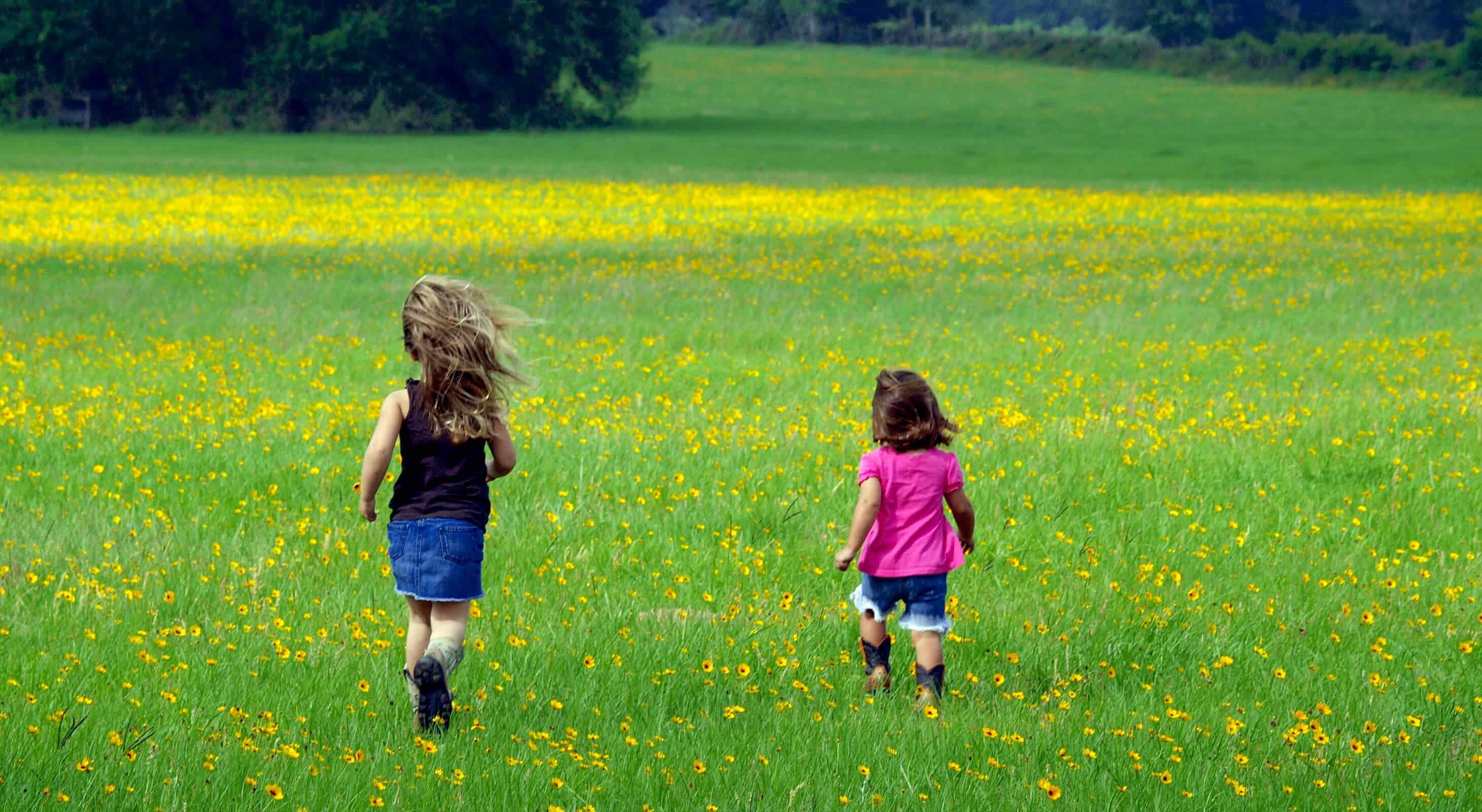 Two girls running through the flowers on a kid friendly vacation in TX