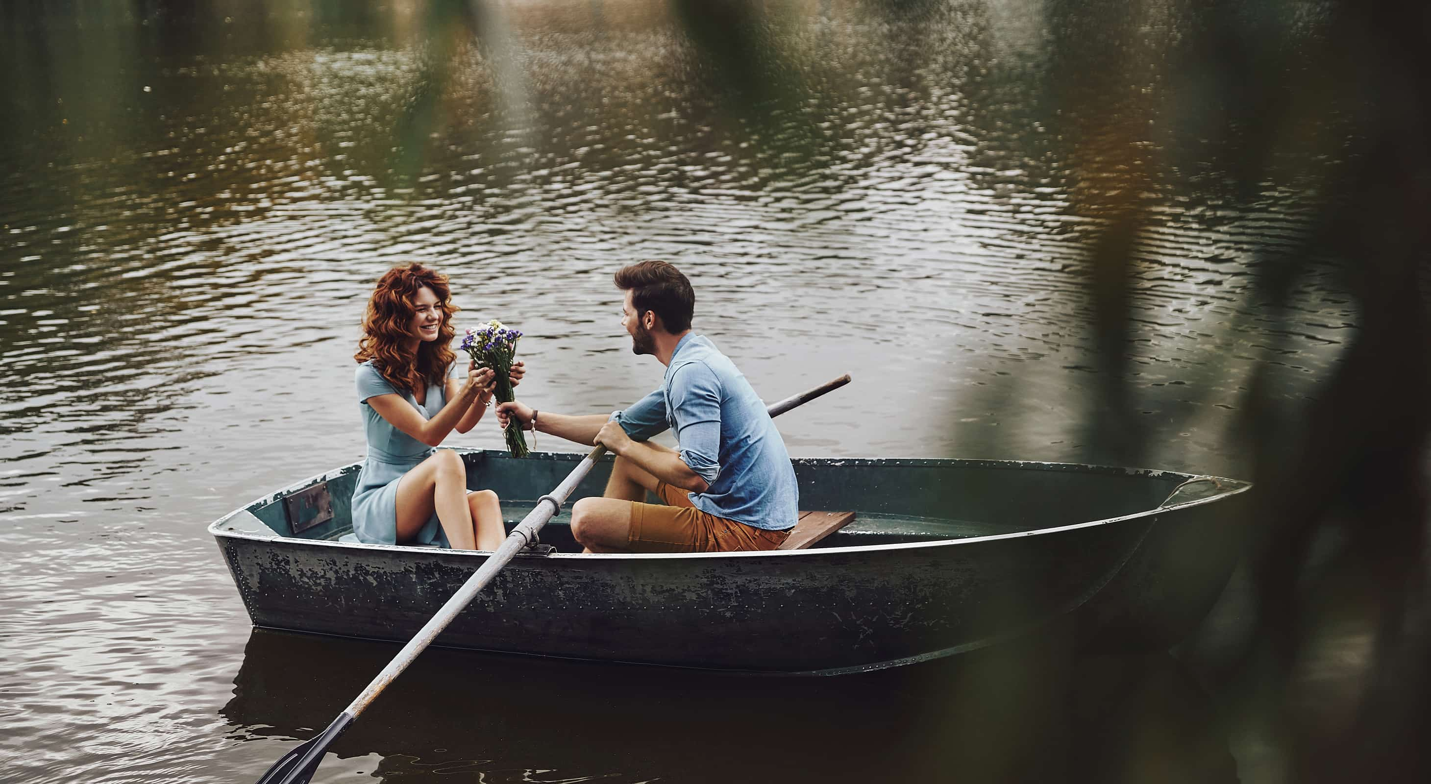 man handing woman flowers in a rowboat on a Teas lake