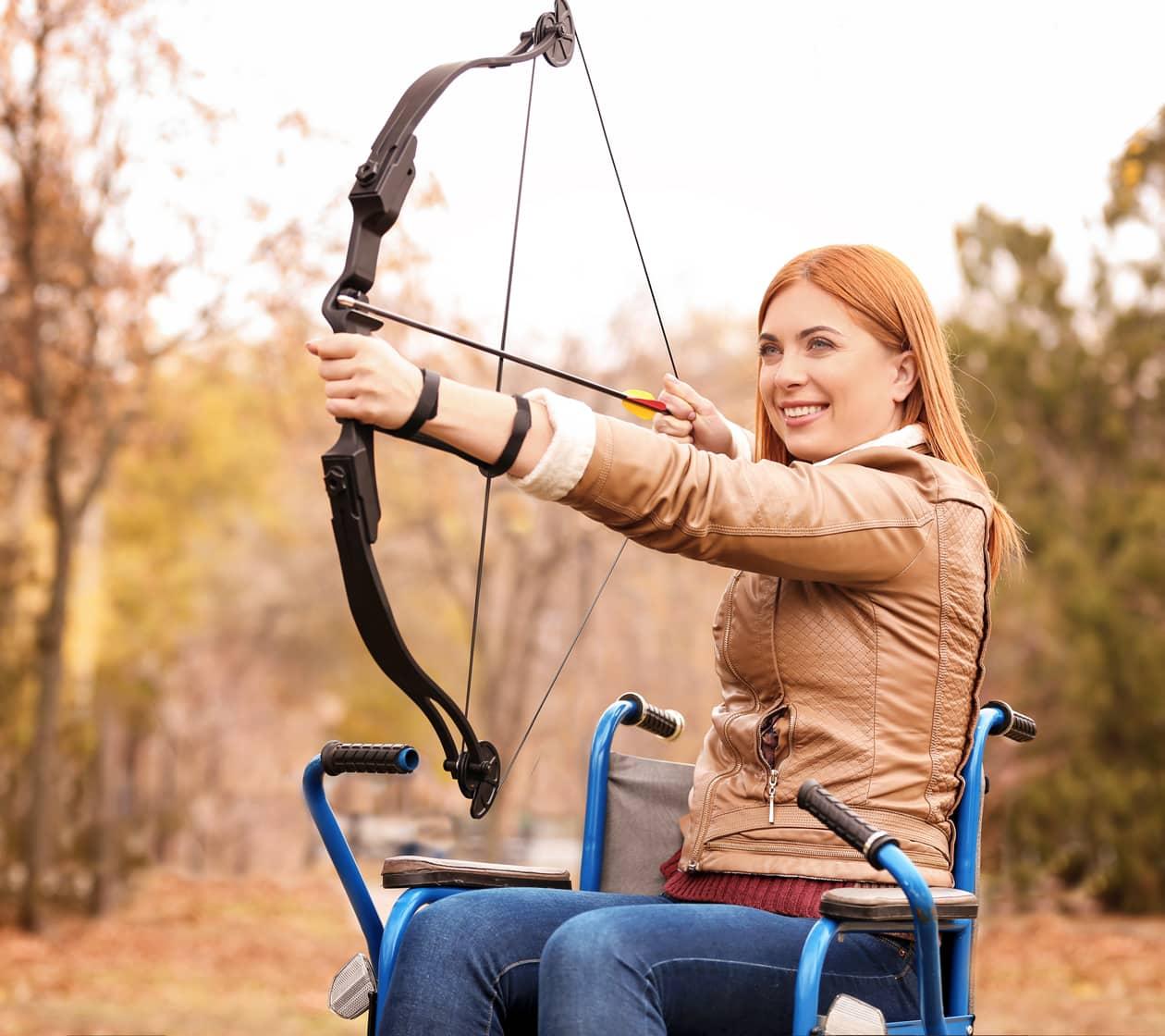 woman in wheelchair doing archery
