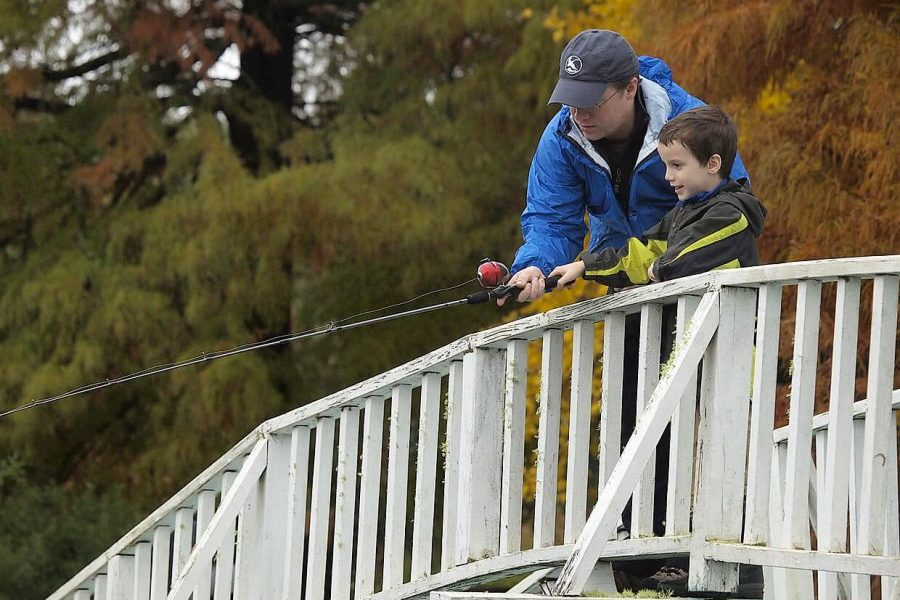 a father and son fishing on a bridge