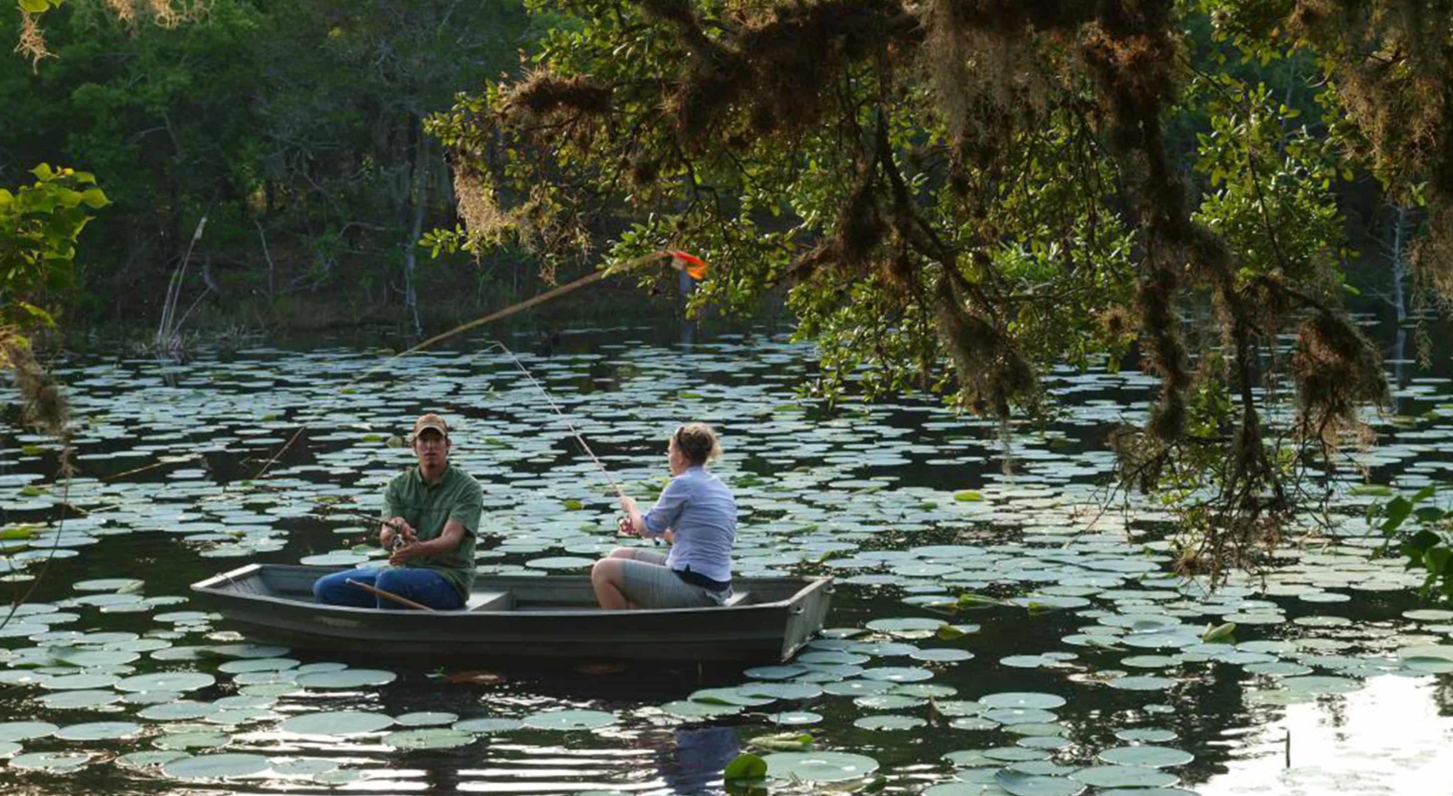 couple in row boat fishing in lake