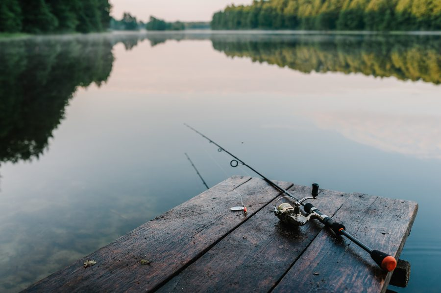 a fishing pole sitting on a dock next to water